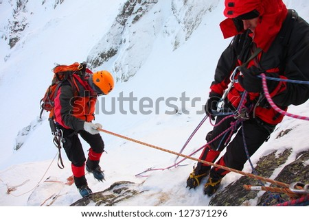 Climber abseiling from the mountain in winter - stock photo
