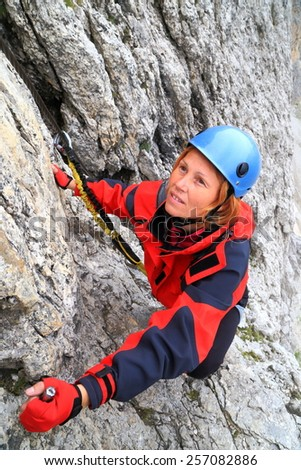 "Climber ascending a steep wall along via ferrata ""Meisules"", Sella massif, Dolomite Alps, Italy - stock photo"