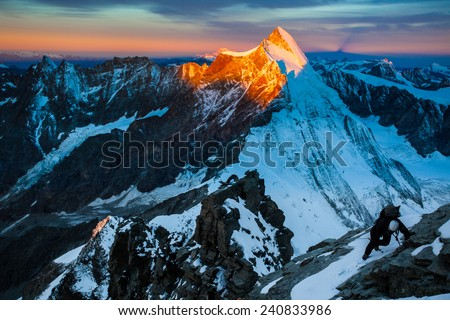 Climber ascending the Lion ridge route (Liongrat) to Matterhorn (Monte Cervino) at dawn - stock photo