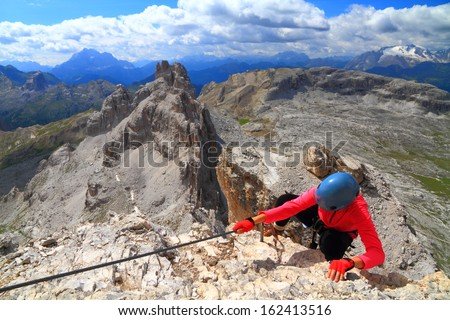 "Climber ascending via ferrata ""Cesco Tomaselli"", Dolomite Alps, Italy - stock photo"