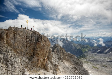 climber at the summit of the Zugspitze, at 2,962 meters above sea level, it is the highest peak of the Wetterstein Mountains as well as the highest mountain in Germany, Europe - stock photo