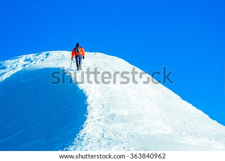 Climber at the top of a snowy summit
