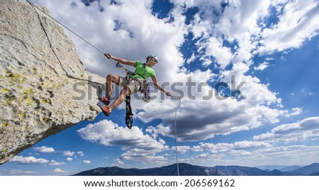 Climber begins her descent on the edge of a challenging cliff.