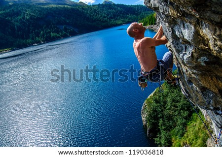Climber climbing a rock wall above Lake Devero, Northern Italy