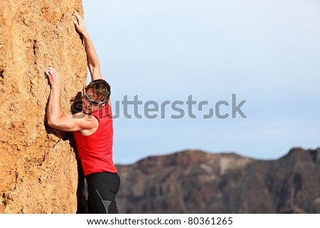 climber climbing looking down during free climbing challenge on vertical rock wall. Young fit, strong male climber with copy space - stock photo
