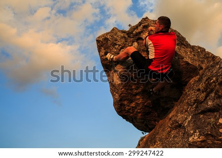 climber climbing on rock.  Strong male climber with copy space - stock photo