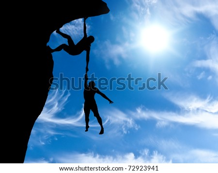 climber clings to a rock plummet with the other hand holding the man - stock photo