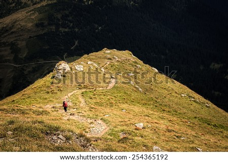 Climber descends the steep slope of mountain - stock photo