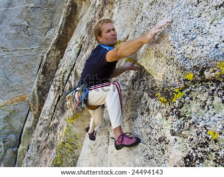 Climber is focused as he clings to a steep rock face in The Sierra Nevada Mountains, California. - stock photo