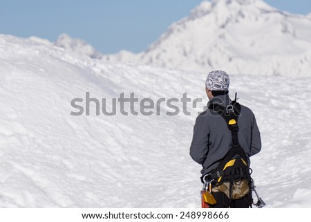 Climber is looking at the snow-covered winter mountain.
