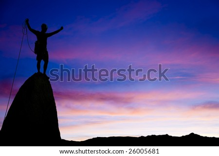 Climber is silhouetted on the summit of a rock spire in the Sierra Nevada Mountains after a successful ascent. - stock photo