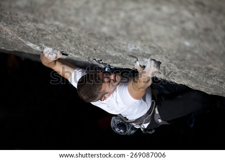 climber making an effort to reach the secure - stock photo