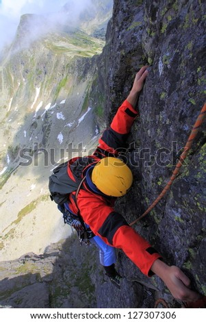 Climber on a steep section on the rock wall, Retezat mountains, Romania - stock photo