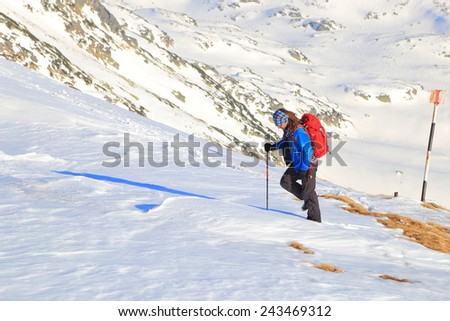 Climber on snow covered mountain slope in sunny day - stock photo