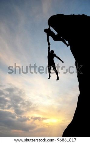 climber on the mountain holding another - stock photo