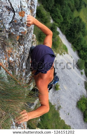 Climber on the rock wall, high above ground