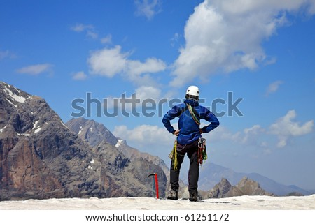 Climber on the snowy mountains with blue cloudy sky - stock photo