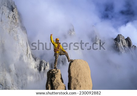 Climber on the summit of a challenging cliff.
