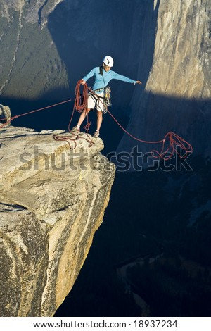 Climber on the summit of a rock monolith in Yosemite National Park, California, on a sunny day. - stock photo