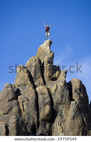 Climber on the summit of a rock spire in the Sierra Nevada Mountains, California, on a summer day. - stock photo