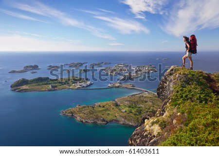 climber on top of rock near bay of ocean - stock photo