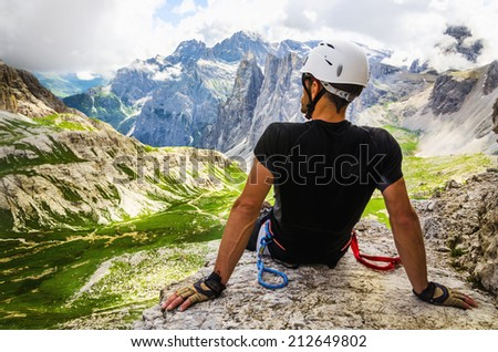Climber on via ferrata Torre di Toblin, resting after the entrance to the top, Sesto Dolomites, Dolomites Mountains, Italy  - stock photo