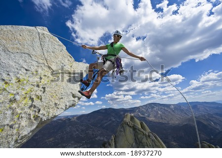Climber rappelling from the summit of a rock spire in The Sierra Nevada Mountains, California, on a cloud filled sky, summer day. - stock photo