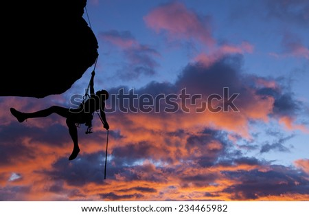 Climber rappells from the summit of a challenging cliff. - stock photo