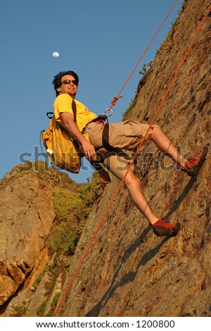 Climber Rappels off a mountain as moon rises - stock photo