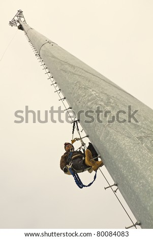 Climber resting in the middle of the climb on the cellular monopole - stock photo