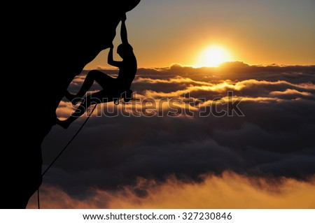 Climber silhouette high above clouds and mountains. Young woman climbing top rope during sunset. - stock photo