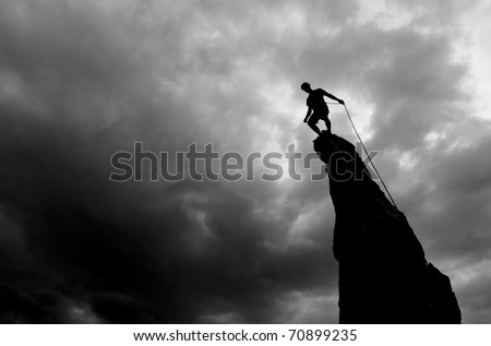 Climber stands on the summit of a rock spire after a successful ascent.
