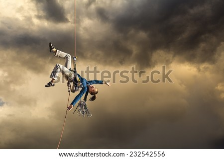 Climber struggles and slips near the summit of a challenging cliff. - stock photo