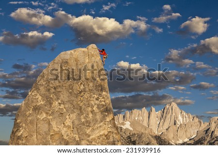 Climber struggles to the summit of a challenging cliff. - stock photo