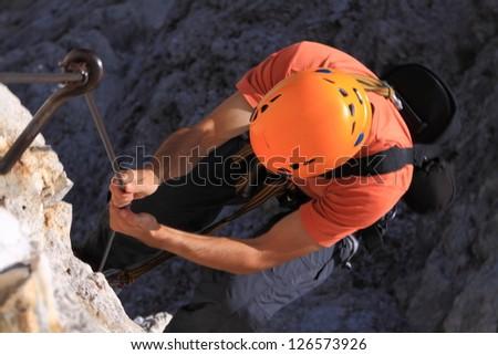 Climber struggling uphill, via ferrata Olivieri, Dolomite Alps, Italy - stock photo
