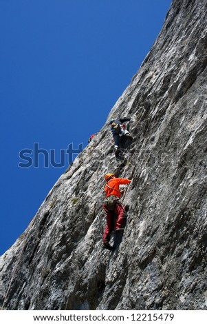 Climber team climbing on rock - stock photo