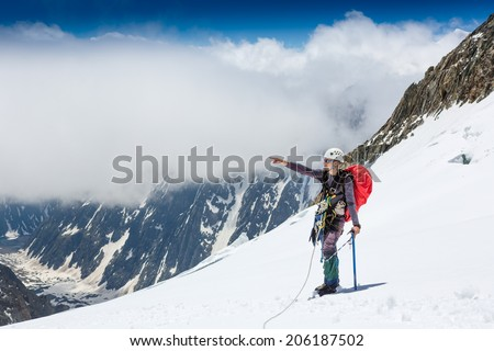 Climber with a backpack and mountain panorama  - stock photo