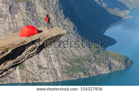 climber with a tent on the rock top