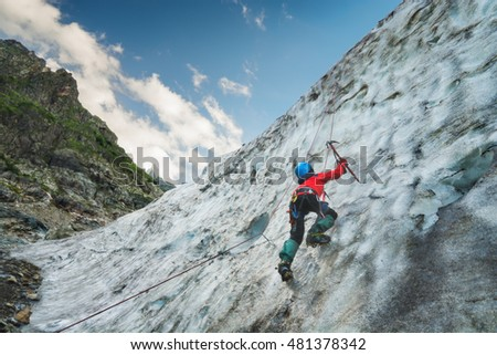 Climber with axe in his hand climbs on a glacier to the top of the mountain. Caucasus, Georgia, Svaneti region.