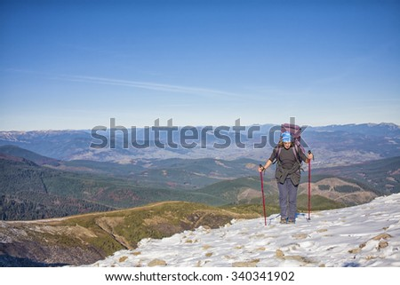 Climber with backpack is the snowy slope.