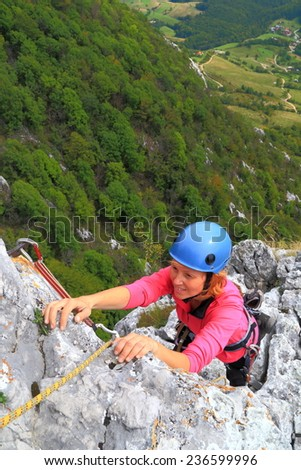 Climber woman ascending a limestone cliff - stock photo