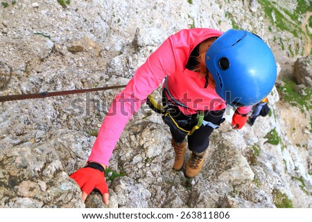 "Climber woman wears protective helmet on via ferrata ""Brigata Tridentina"", Sella massif, Dolomite Alps, Italy - stock photo"