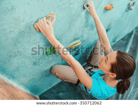 Climber young woman starting bouldering track on artificial wall indoor, top view