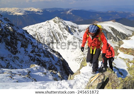 Climbers ascending a narrow ridge above snow covered mountains - stock photo