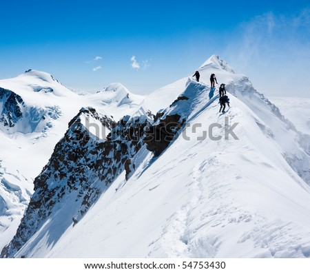 Climbers balancing in blizzard on a narrow ridge of Lyskamm (aka Maneater, 4480 m)