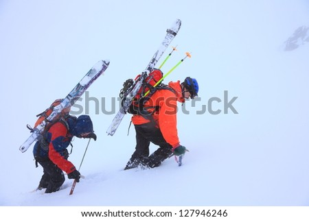 Climbers carrying skies and ascending a snow covered mountain slope in bad weather - stock photo