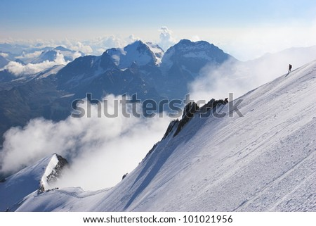 Climbers descend a ridge of snow high in the Swiss Alps, with clouds and mountain peaks in the background. - stock photo