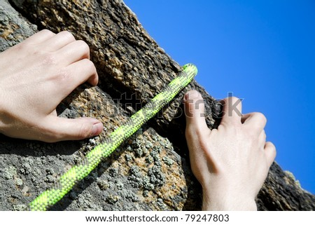 climbers hands and rope on bring of rock