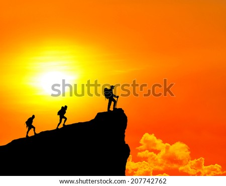climbers standing on summit of mountain. - stock photo