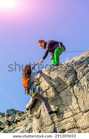 Climbers teamwork. Two climbers reaching summit one holding hand of her partner assisting to make last step to top young female athletes natural stone rock blue sky and shining sun on background - stock photo